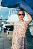 拿着小船的花礼服和太阳镜的白肤金发的女孩航行 免版税图库摄影