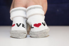 拿着小婴孩袜子的手 库存照片