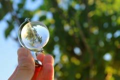 拿着小水晶地球的男性手 免版税库存照片