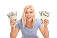 拿着少量堆金钱的极度高兴的妇女 免版税库存照片