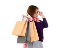 拿着少量购物袋的头疼妇女 免版税库存照片