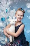 拿着山羊小雕象的美丽的小女孩 免版税库存照片
