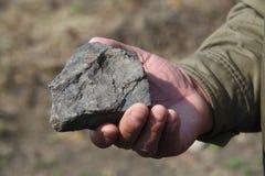 拿着岩石的手 免版税库存照片
