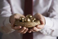 拿着巢的商人有很多金黄鸡蛋 免版税库存图片