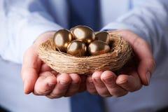 拿着巢的商人有很多金黄鸡蛋 库存照片