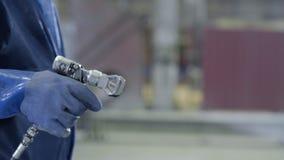拿着工业大小喷枪的武装的手使用为工业绘画和涂层 拿着油漆浪花的男性手 免版税库存照片