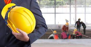 拿着工作者安全的工程师黄色盔甲 免版税库存图片