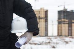 拿着工作者安全的建筑师或工程师黄色盔甲在新的高层住宅背景和 免版税库存照片