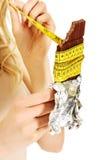 拿着巧克力和吃措施磁带的少妇 库存照片