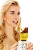 拿着巧克力和吃措施磁带的少妇 免版税图库摄影