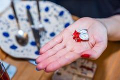 拿着巧克力在空的使用的五颜六色的板材的女性手甜点套有叉子匙子和刀子的在被吃的食物以后  免版税图库摄影