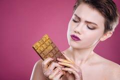 拿着巧克力块的宜人的少妇 库存照片