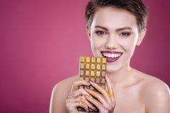 拿着巧克力块的快乐的妇女 免版税库存照片