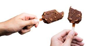 拿着巧克力杏仁冰淇凌叮咬在白色背景的手酒吧孤立 库存照片