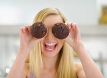 拿着巧克力松饼的愉快的少年女孩 免版税图库摄影
