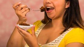 拿着巧克力果仁巧克力蛋糕,使用叉子的劫掠的叮咬的小板材深色的妇女,显示对照相机,酥皮点心 免版税图库摄影