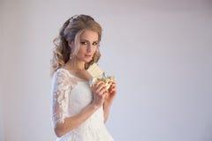 拿着巧克力的婚礼礼服的新娘 免版税库存照片