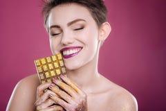 拿着巧克力的快乐的妇女 库存图片