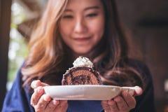 拿着巧克力蛋糕卷和打好的奶油与感觉的一名美丽的亚裔妇女愉快和好生活方式 库存照片