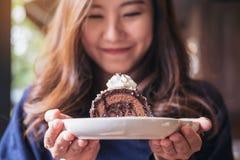 拿着巧克力蛋糕卷和打好的奶油与感觉的一名美丽的亚裔妇女愉快和好生活方式 免版税库存照片