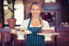 拿着巧克力蛋糕和杯形蛋糕的俏丽的女服务员 库存图片
