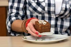 拿着巧克力蛋糕的女性手 免版税图库摄影
