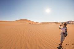 拿着巧妙的电话和拍照片的游人在风景沙丘在Sossusvlei,纳米比亚沙漠, Namib Naukluft国家公园, Namib 免版税库存图片