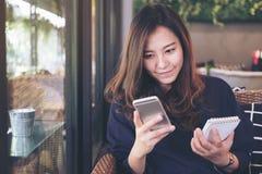 拿着巧妙的电话和笔记本的一个美丽的亚裔女商人,当工作在现代咖啡馆时 免版税库存照片