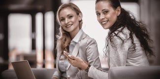 拿着巧妙的电话和膝上型计算机的微笑的女实业家 免版税库存照片