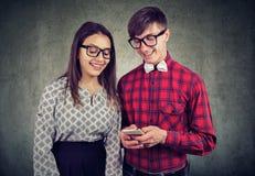 拿着巧妙的电话的愉快的eccentic行家人,显示他的女朋友滑稽的图片 免版税库存图片