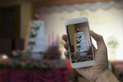 拿着巧妙的电话的手在婚礼大厅拍照片 库存图片