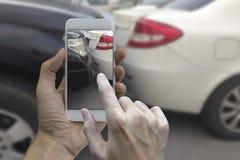 拿着巧妙的电话的手在汽车cras的现场拍照片 免版税图库摄影