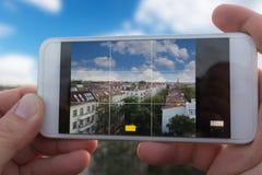 拿着巧妙的电话的手拍城市地平线的照片 免版税库存图片