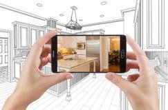 拿着巧妙的电话的手显示厨房图画照片是 免版税库存照片