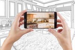 拿着巧妙的电话的手显示厨房图画照片是 免版税库存图片