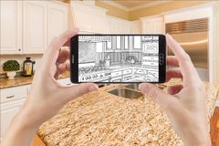 拿着巧妙的电话的手显示厨房照片图画是 免版税库存图片