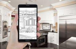 拿着巧妙的电话的手显示厨房照片Beh图画  库存图片