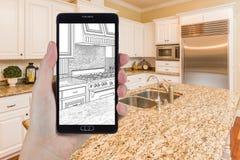拿着巧妙的电话的手显示厨房照片Beh图画  免版税图库摄影