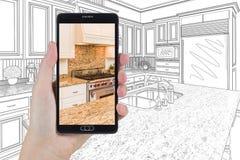 拿着巧妙的电话的手显示画Beh的厨房照片 库存照片