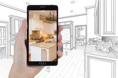 拿着巧妙的电话的手显示画Beh的厨房照片 库存图片