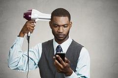 拿着巧妙的电话的执行委员,烘干他的头发  图库摄影