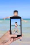 拿着巧妙的电话的游人拍照片 免版税库存图片