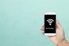 拿着巧妙的电话/白色手机有wifi的手在黑屏幕上连接 库存照片