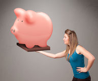 拿着巨大的储款存钱罐的女孩 免版税库存照片