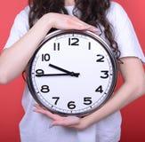 拿着巨大的办公室时钟的女孩画象反对红色背景 库存图片