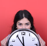 拿着巨大的办公室时钟的女孩画象反对红色背景 库存照片