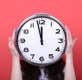 拿着巨大的办公室时钟的女孩画象反对红色背景 免版税图库摄影