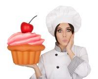 拿着巨大的杯形蛋糕的惊奇妇女点心师 库存照片
