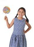 拿着巨大的棒棒糖的拉丁女孩愉快和激动在逗人喜爱的蓝色礼服和马尾糖果概念 图库摄影