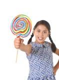 拿着巨大的棒棒糖的拉丁女孩愉快和激动在逗人喜爱的蓝色礼服和马尾糖果概念 免版税库存图片